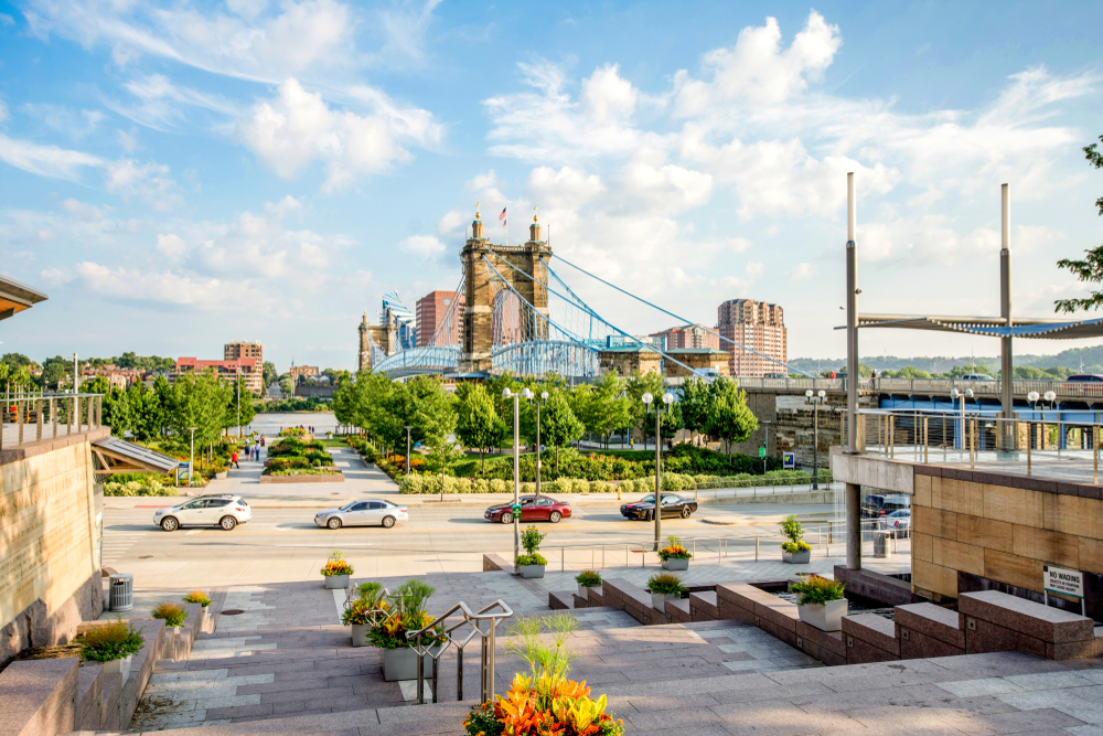 The view of the Smale Riverfront Park near the John A. Roebling Suspension Bridge in Cincinnati. There are trees, shrubs, stone walkways, and stone steps.