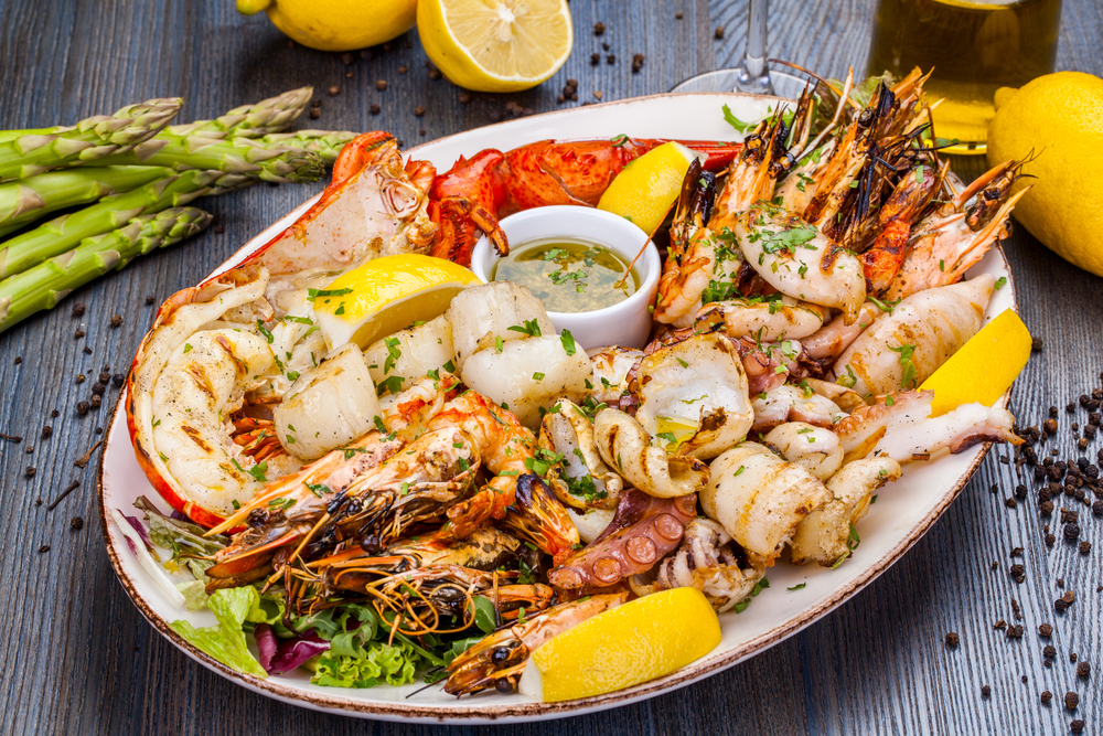 A large white plate on a gray wooden table that is full of seafood. There is squid, shrimp, lobster, a bowl of butter, and slice lemon.