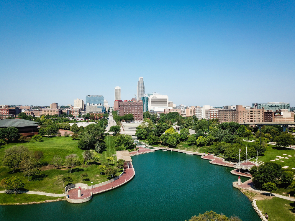 A view of the Omaha Nebraska skyline on a sunny day. You can see a body of water with a brick path around it, lots of trees and a park like area. In the distance there are taller buildings.