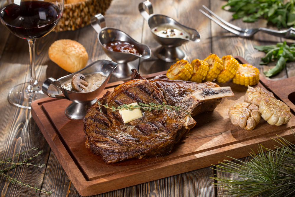 A wooden platter on a wooden table that has a large steak on it. The steak is from one of the steakhouse restaurants in Omaha. Also on the platter is grilled corn, garlic, and different gravy boats. You can also see a roll and a glass of wine on the table.