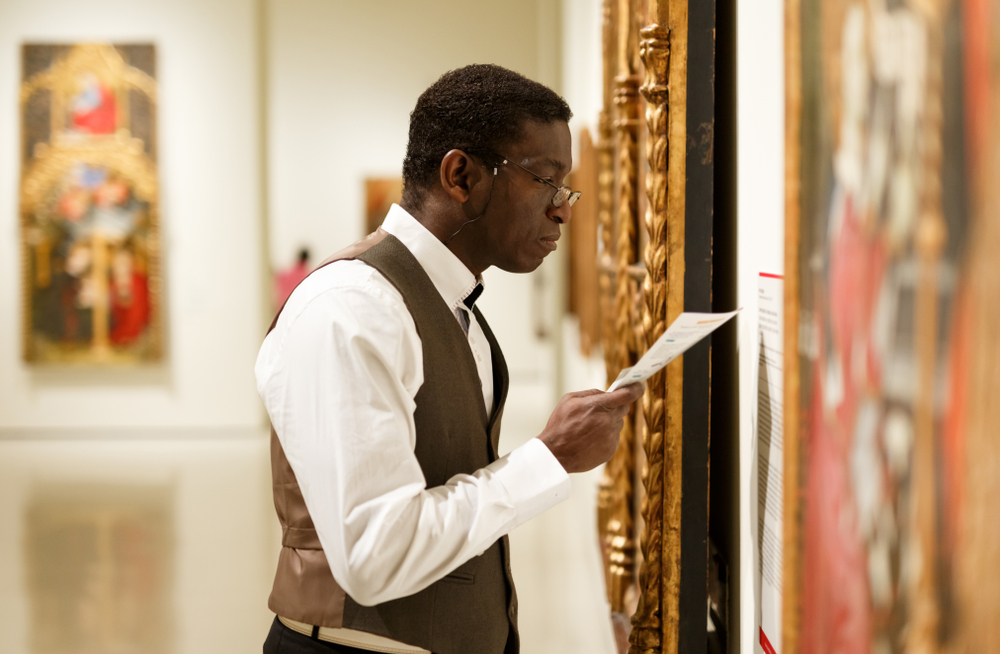 A man in a white shirt and brown vest looking closely at art in ornate gold frames in an art museum.
