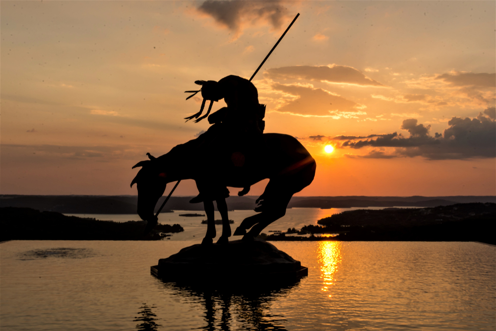 An American Native Indian Staue riding a horse at sunset at top of the hill in Branson