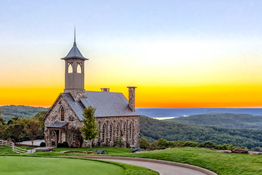 A church at the top of the hill with mountains and sunset in the background