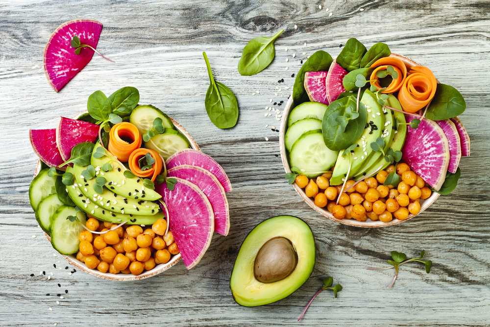 Two bowls on a light gray wood table. The bowls are vegan bowls from one of the vegan restaurants in Omaha. You can see sliced avocado, cucumbers, squash, spinach, chickpeas, and a pink fruit in the bowl.