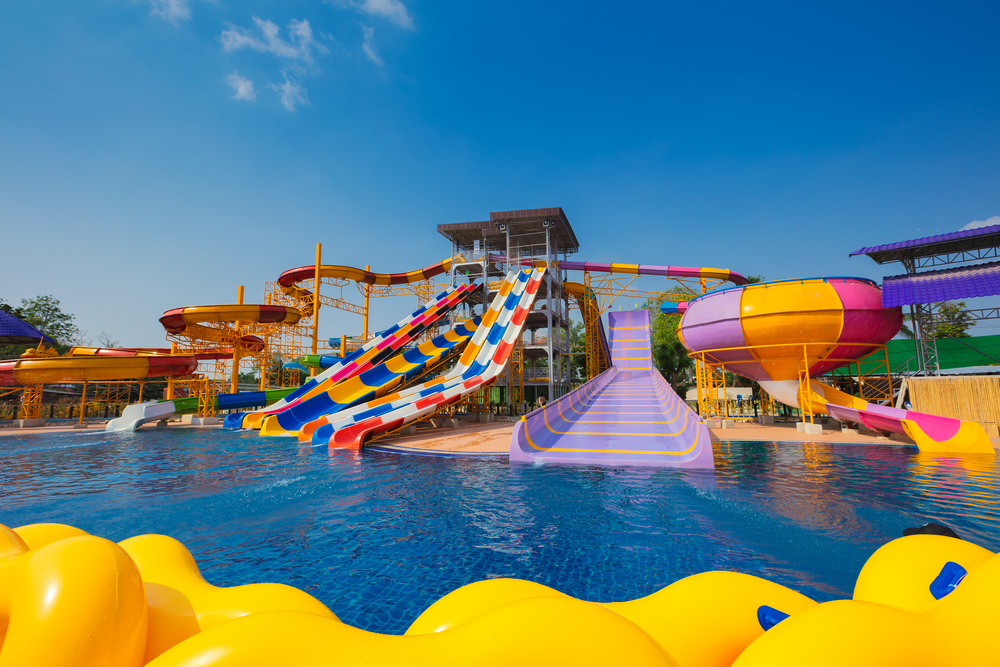 A set of different sized waterslides that go into a large pool at a waterpark. The waterslides are all different colors, some are striped and some are solid.