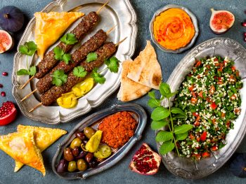 A spread of Middle Eastern food. There is kabobs, a quinoa salad, hummus, pita, pomegranates, and figs. The foods are on silver dishes. Its similar to meals you find in restaurants in Detroit.
