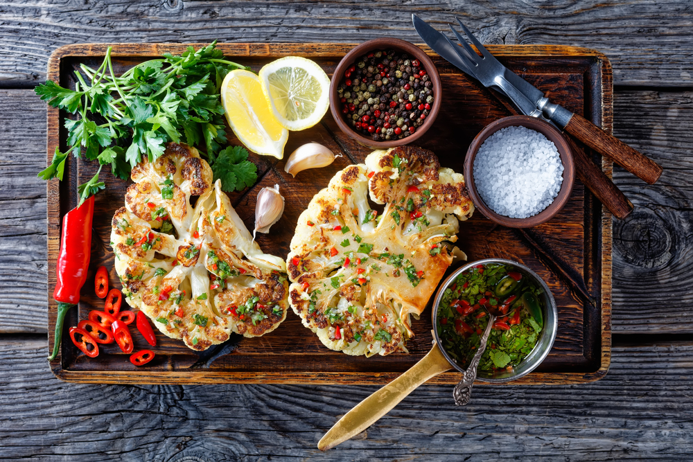 Grilled cauliflower steaks with dressings on a wooden board in an article about restaurants in Duluth