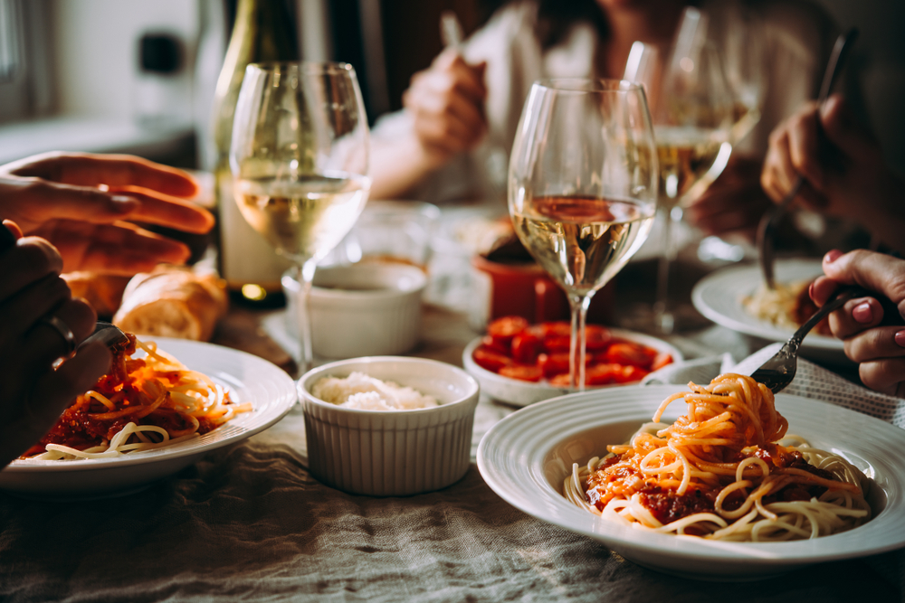 Three people eating pasta around a table with wine
