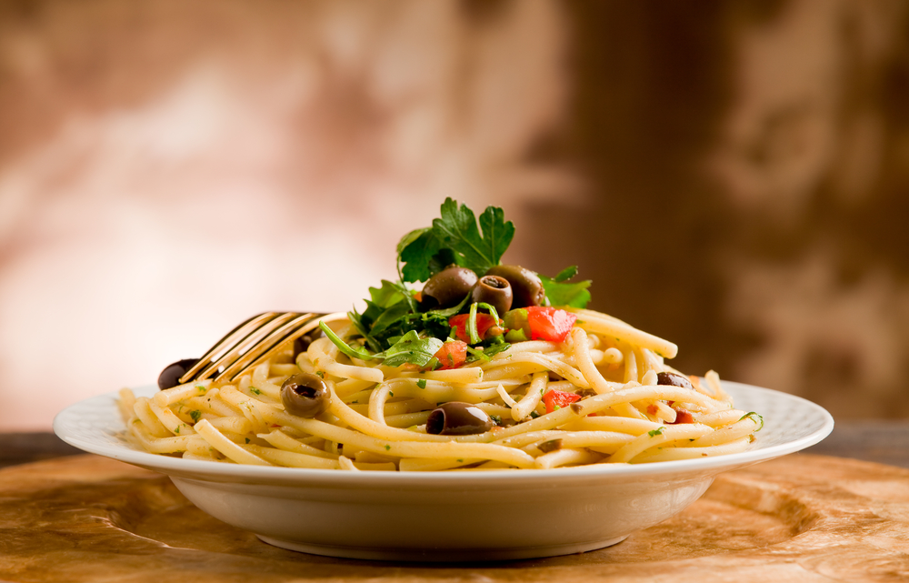 A dish of pasta with olives on top and a fork resting on it.