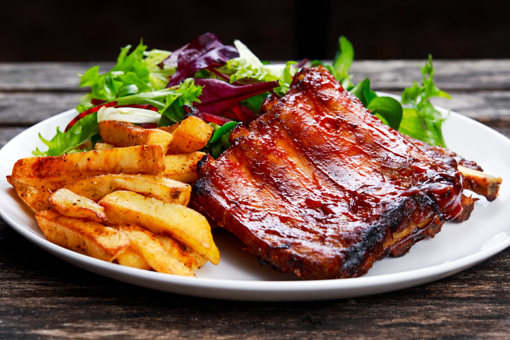Roasted ribs and fries on a plate with salad.
