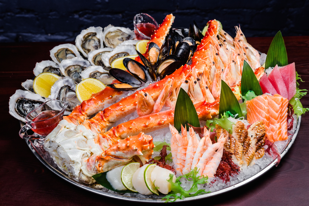A large seafood platter over ice with mussels, lobsters and other fish