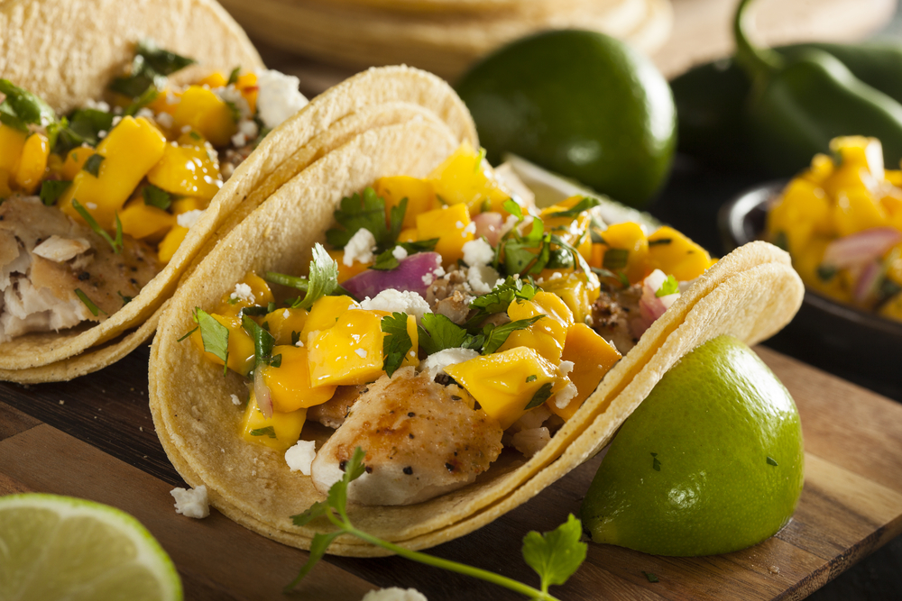 Fish tacos with mango and lime on a wooden board
