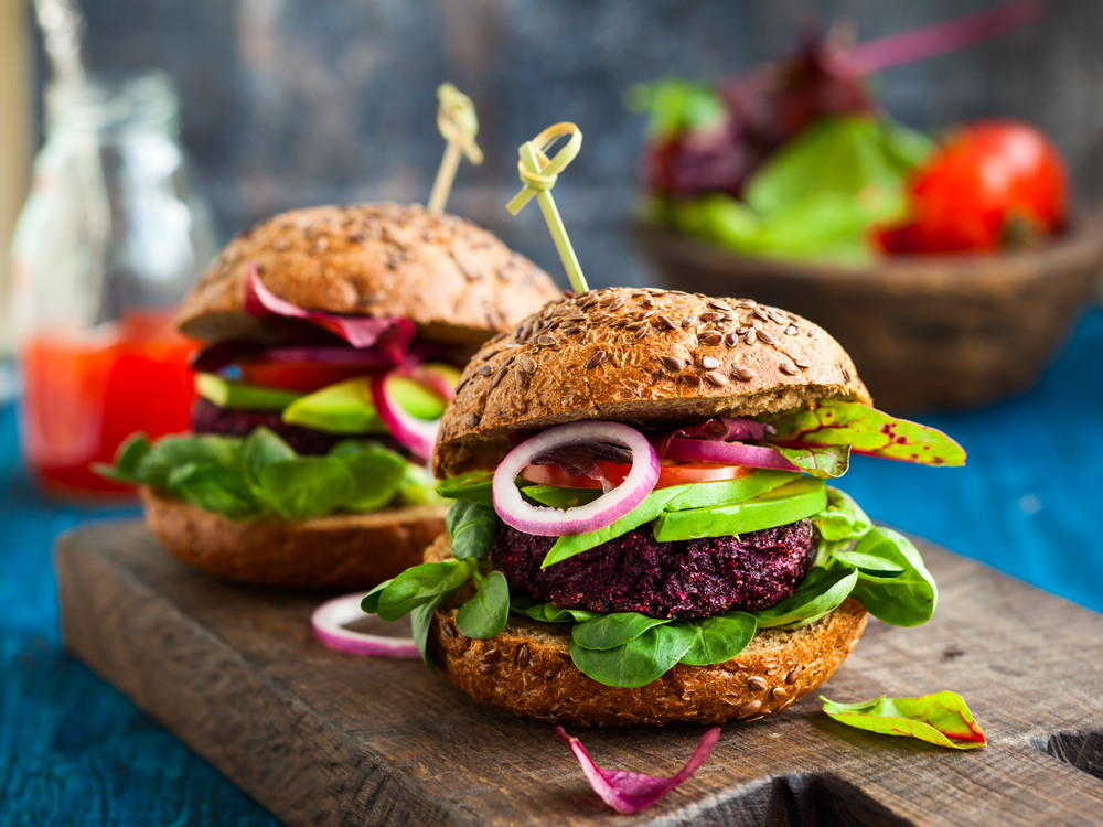 Beet Burger with salad with wholegrain bun is served up at one of the best plant-based restaurants in Kansas City MO.