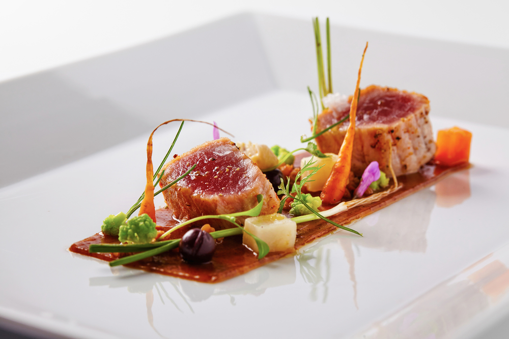 A small fine dining plate with two small pieces of tuna and vegetable in an article about restaurants in Kansas City