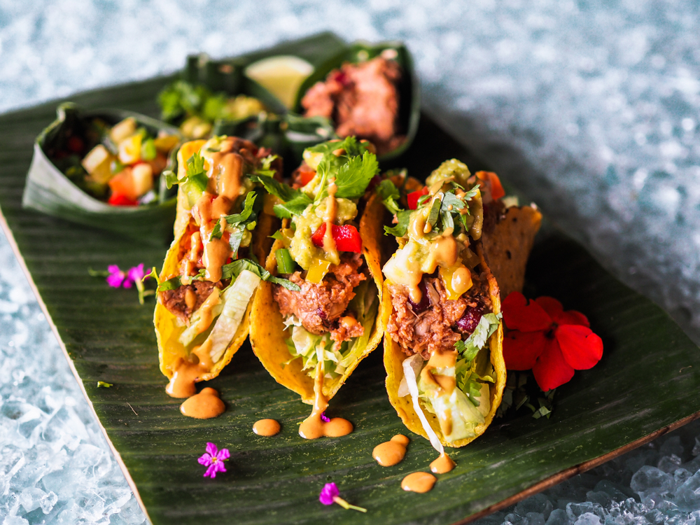 Jackfruit tacos with lettuce and salad on a green plate