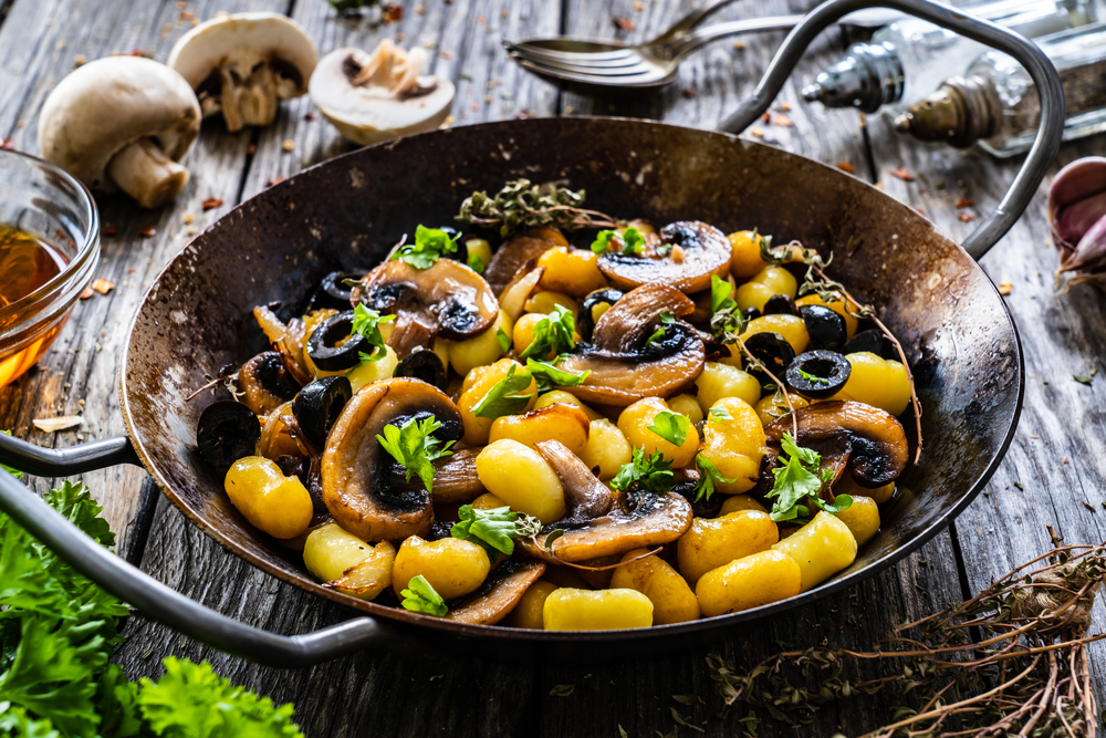 Gnocchi with friend mushrooms in a plan with mushrooms around it