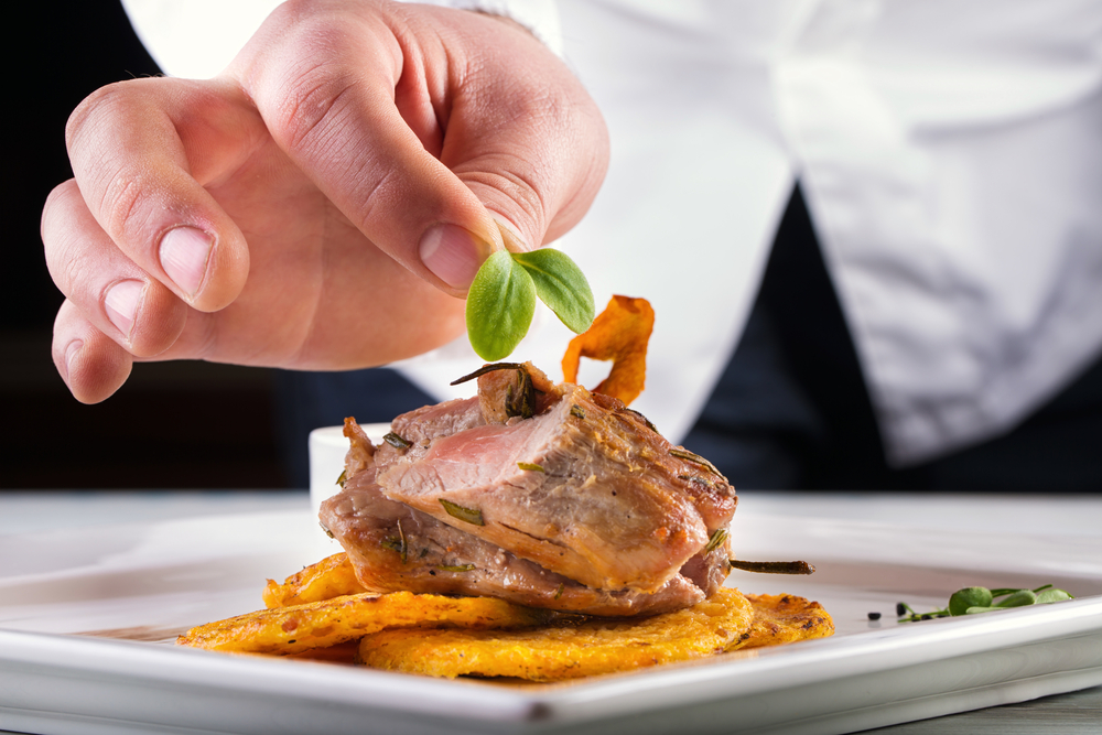 A chef putting a garnish on top of a plate of food containing meat in an article about restaurants in Kansas City
