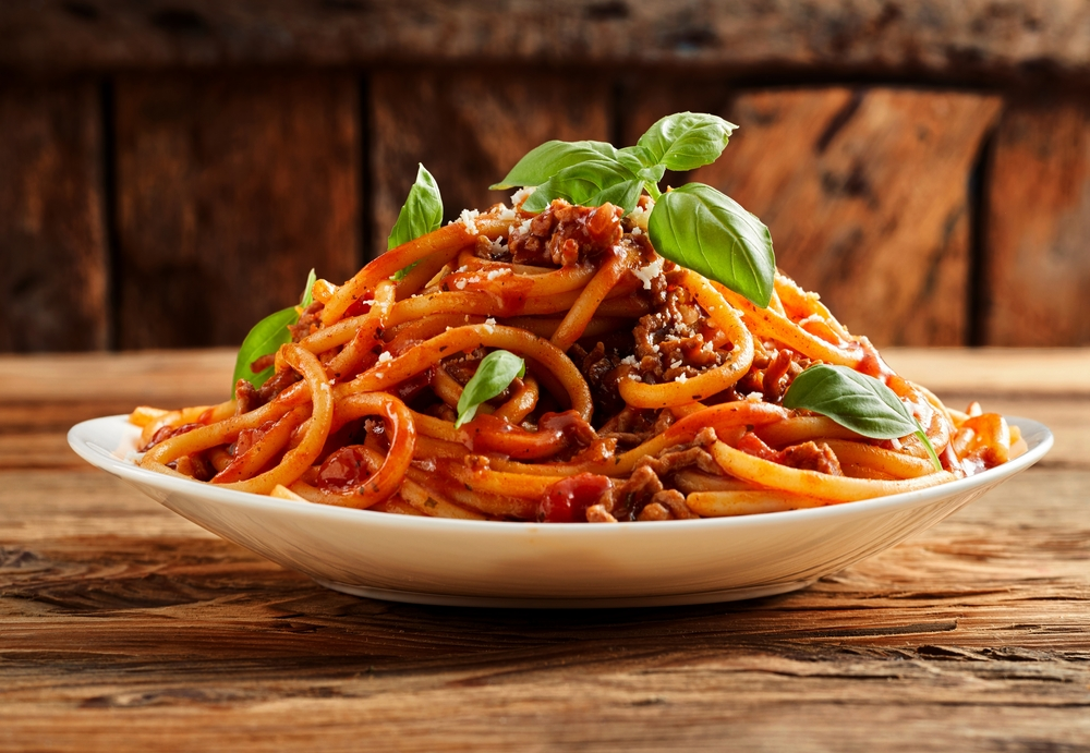 A heap of spaghetti Bolognese on a palate with a garnish on top served from a top Kansas City restaurant.