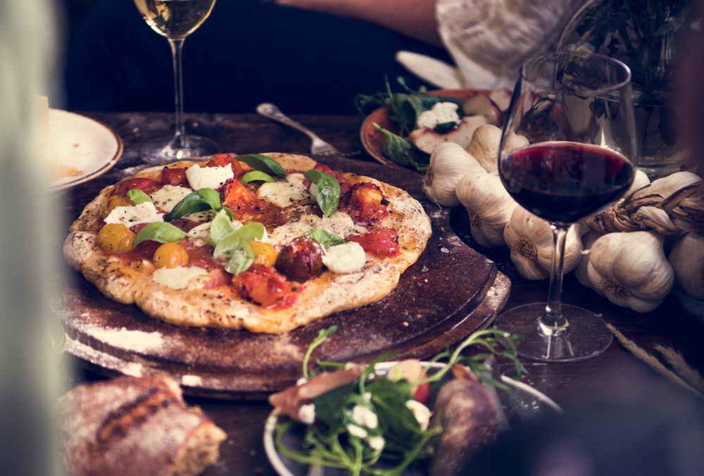 Vegetable pizza on a board on a table with a glass of red wine served at classy KCMO restaurant.