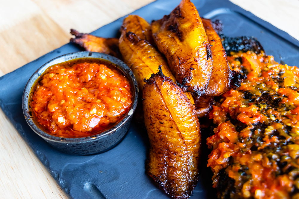 Friend slices of plantain on a plate with a dipping sauce