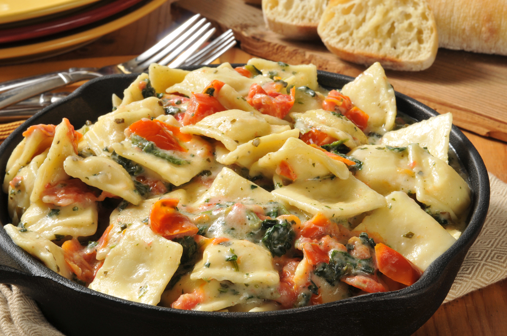 Ravioli in a dish with tomatoes and olives in an article about restaurants in Kansas City