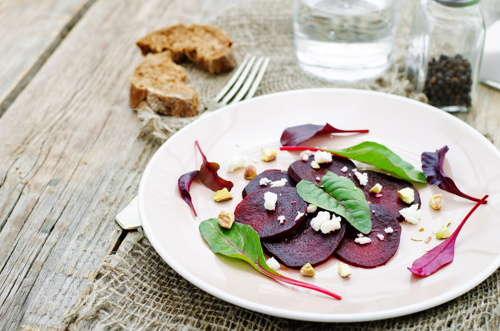 Sliced beetroot on a plate with salad leaves and crumbled cheese