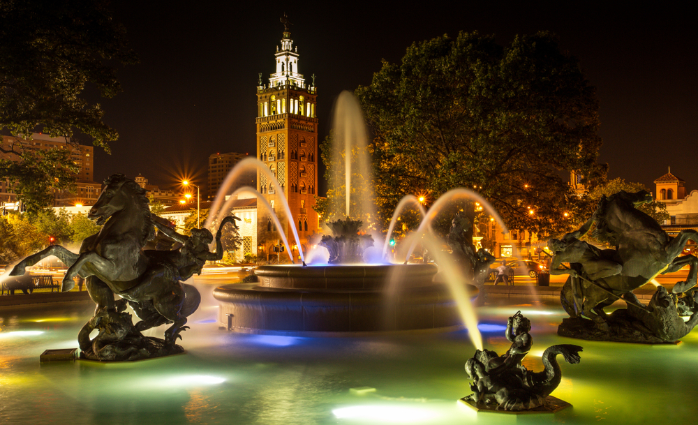 A fountain with statues and a building with a tower in the background in Kansas City