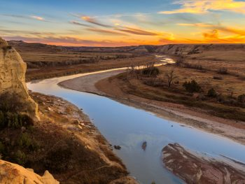 River flowing from the middle of plains during sunset