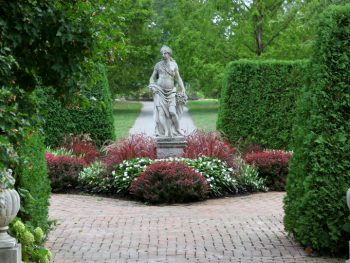 A statue on a path surrounded by foliage and hedges